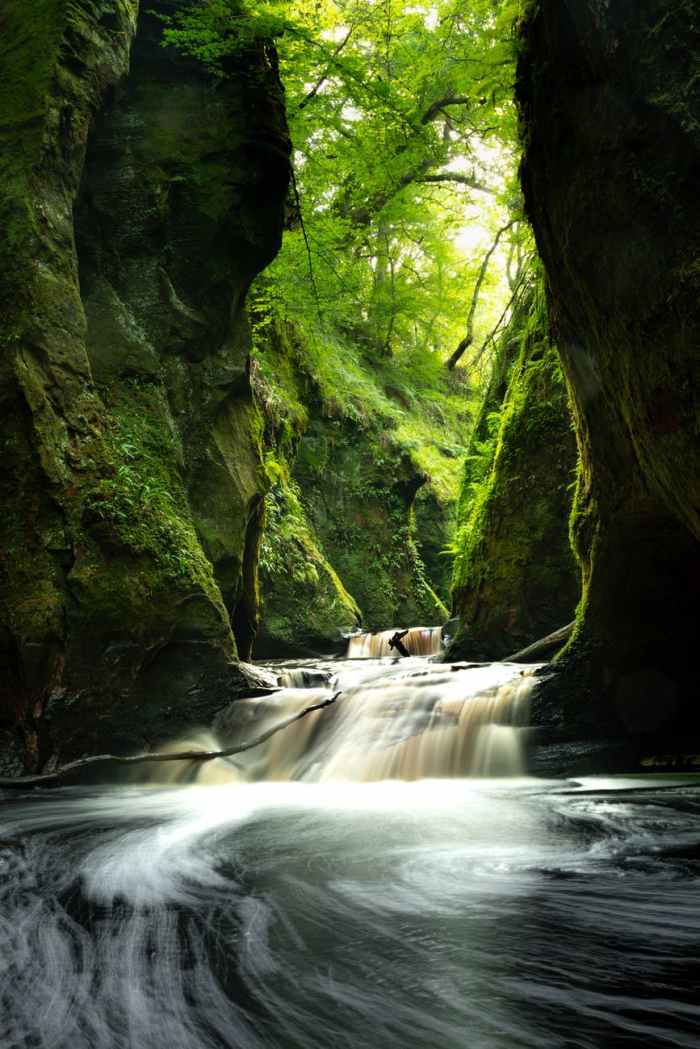 time lapse photo of river between mossy rocks