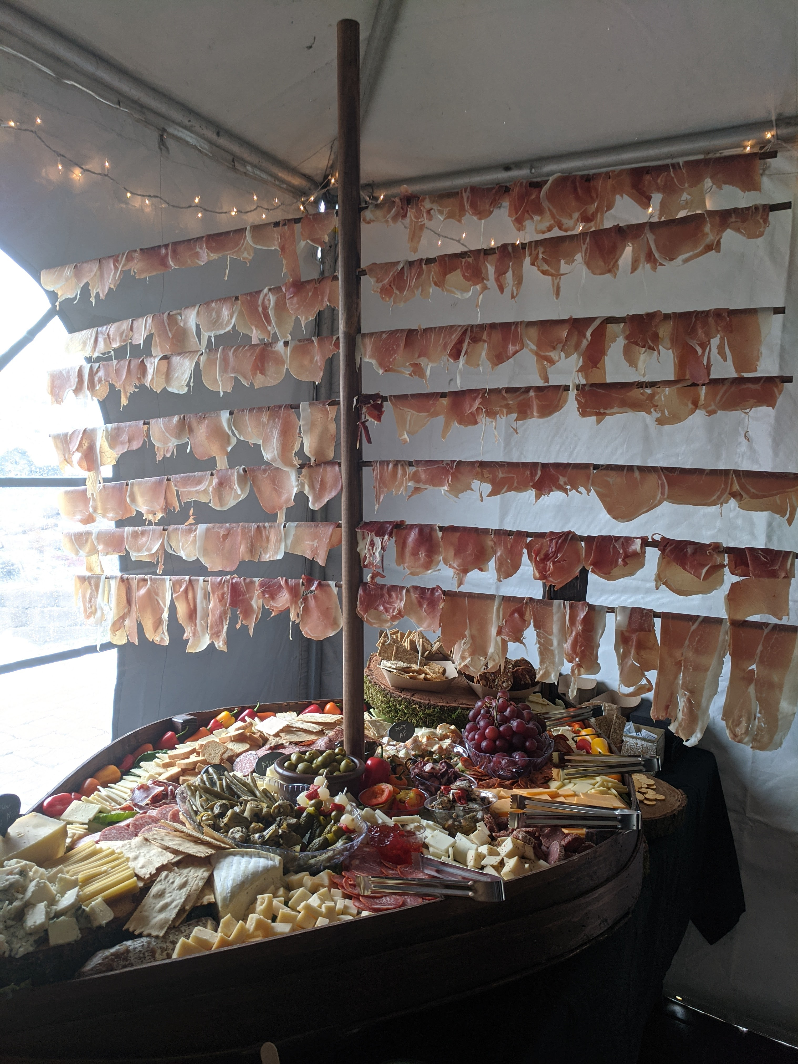 A replica viking longboat loaded up in charcuterie. From the 4-foot tall mast hangs shaved prosciutto. The base of the boat has cured meats, pickled vegetables, and various cheeses.