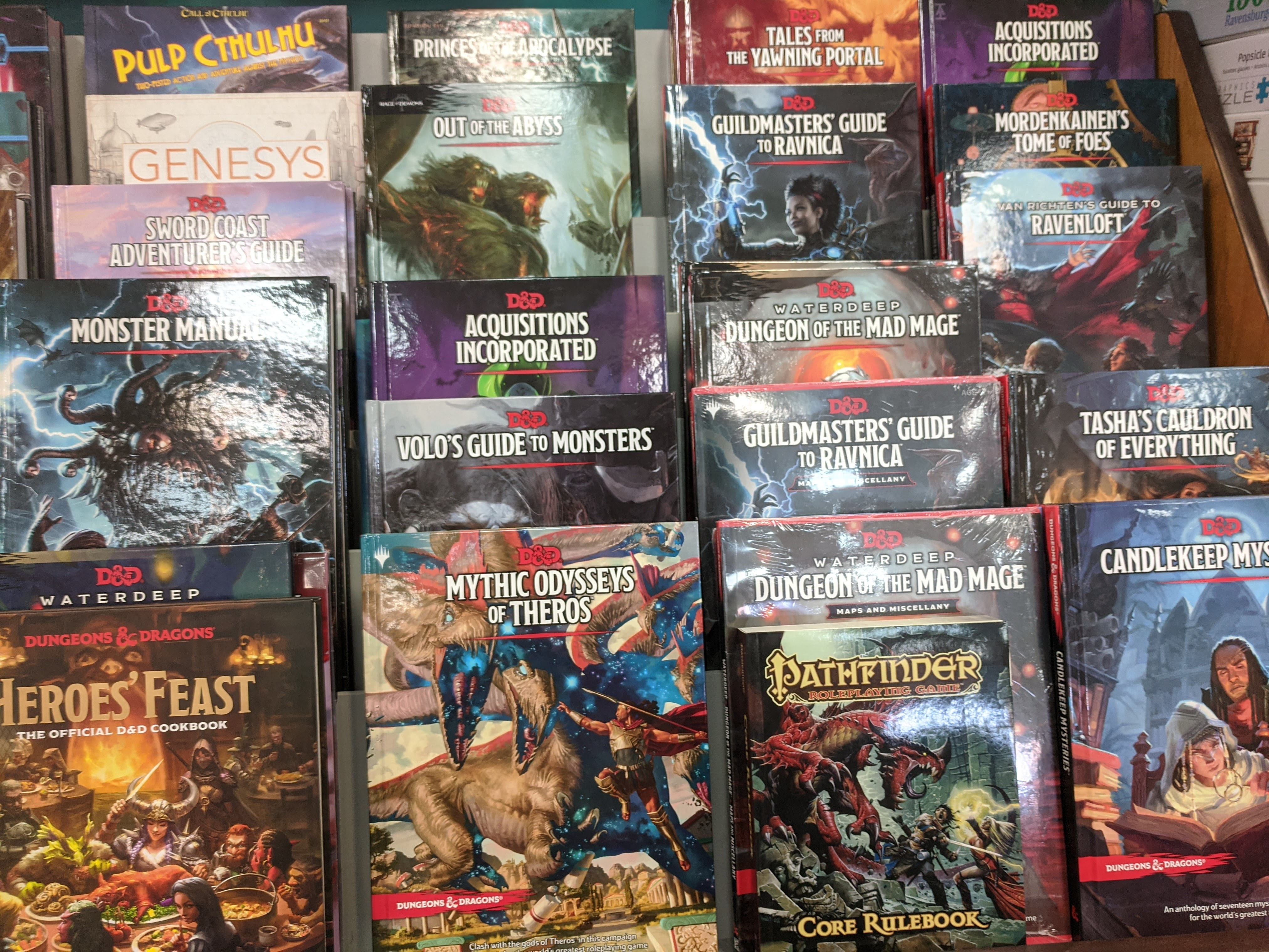 A photo of a bookshelf with 21 different D&D titles, as well as three other RPG books.